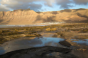 Late afternoon light on beach and cliffs La Caleta de Famara, Lanzarote, Canary islands, Spain