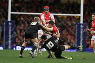 Lee Byrne of Wales is stopped by Daniel Braid (19) and Dan Carter (10) of the Allblacks. Invesco Perpetual match, Wales v New Zealand at the Millennium stadium in Cardiff on Sat 27th Nov 2010.  pic by Andrew Orchard, Andrew Orchard sports photography,
