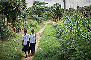 "Esperance Mulwefakadi (right) and Sabine walks home from Bana Kimono primary school, Kikwit, Bandundu Province, Democratic Republic of Congo on November 14, 2014. Esperance received a scholarship through the program 'VAS-Y Fille' and has been able to continue the last two years of school. From a disadvantaged family, her mother has been sick and bed ridden for many years and her father and extended family whom she lives with scrape by collecting manyok roots which they dry and sell to make a meagre living. ""I would like to continue my studies into high school if my family has the means to support me and I dream of one day becoming a nurse."" The Bana Kimono primary school has 394 students with 40 in total female students receiving a scholarship from years 5 & 6. CRS with partner Caritas and organisations International Rescue Committee and Save the Children are engaged in a education initiative focusing on assisting female students from financially disadvantaged families continuing studies in the final two years of primary school. The program 'VAS-Y Fille' or 'Go Girl!' supplies scholarships to help pay the school fees and books for students from disadvantaged families."
