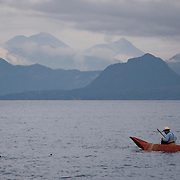 A fisherman uses nets to catch small fish in Lago de Atitlan, Guatemala. The lake is surrounded by volcanos on all sides.  July 2009.  (Photo/William Byrne Drumm)