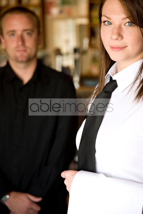 Portrait of a waitress standing next to a waiter
