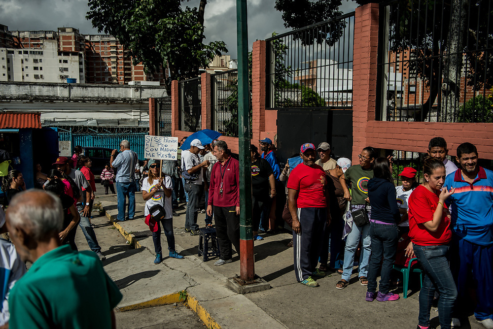 CARACAS, VENEZUELA - JULY 30, 2017:  Government supporters wait in line to vote for candidates for the new National Constituent Assembly, in elections called by Socialist President, Nicholás Maduro. Lines across Caracas were significantly shorter than those of the opposition's July 16th symbolic vote. Many fear this election will turn Venezuela similar to Cuba. Opponents of the government criticize President Maduro for calling for this election - saying the new assembly is a power grab, and will be a puppet of the President - the only candidates on the ballot are government loyalists. Critics also fear the new assembly will turn the country into a dictatorship, re-write the constitution and wipe out the democratically elected and opposition controlled congress. There have been widespread reports of voter intimidation, and of the government threatening state workers and citizens that receive government benefits like subsidized food - who report the government telling them they are obligated to vote, and if they don't, they will lose their jobs and benefits. Thousands have taken to the streets to protest the election in the days leading up to the July 30th vote.  PHOTO: Meridith Kohut for The New York Times