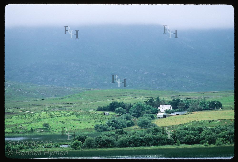 Mist-veiled mountains loom over farmstead along backwaters of Lough Corrib; eastern Connemara. Ireland