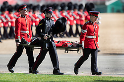 © Licensed to London News Pictures. 13/05/2019. London, UK. A guardsmen is carried away on a stretcher during rehearsals for Trooping of the Colour ceremony in bright sunshine in Horse Guards Parade. The ceremony - on June 8, 2019 - heralds the birthday of Queen Elizabeth II. Photo credit: Peter Macdiarmid/LNP