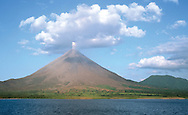 Arenal Volcano in eruption. Lake Arenal in foreground. Costa Rica.<br />