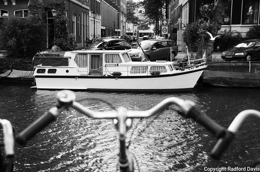 Bicycle along the canals of Amsterdam, The Netherlands. Black and white.