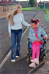 Care manager and young woman with Cerebral Palsy together in park,