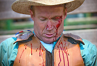 "Mark Wilson waits to be examed by Jackson Hole Fire/EMS after being tossed from a bronc while riding in the bareback event at the Jackson Hole Rodeo. Wilson had no other injuries other than the cut above his eye. ""I don't know if it'll make me look any worse,"" Wilson said. ""I was pretty beat up already."""