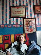 A teenage boy sitting in a room with Coca Cola wallpaper and Arsenal picture, UK, 2000's