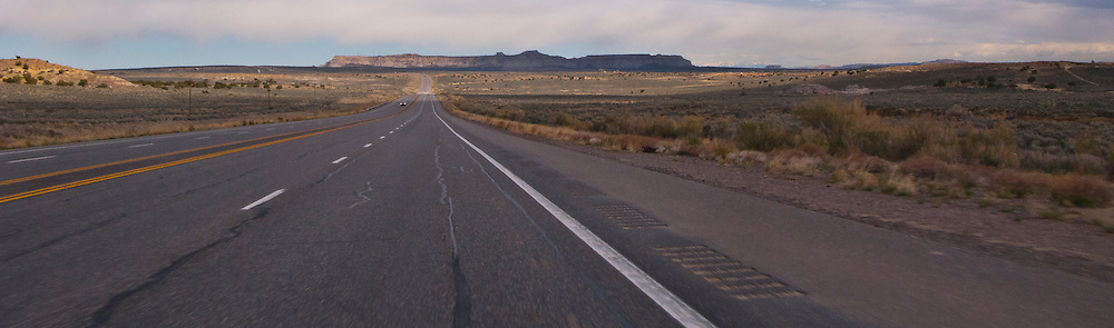 lonely US highway stretches across arid land in NW New Mexico toward a mesa on the horizon.  panorama
