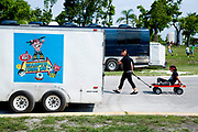 A guy being pulled on a trolley by his friend. Vans Warped Tour, USA touring punk rock music festival, Bicentennial park, Miami, Florida, USA. 24th June 2006