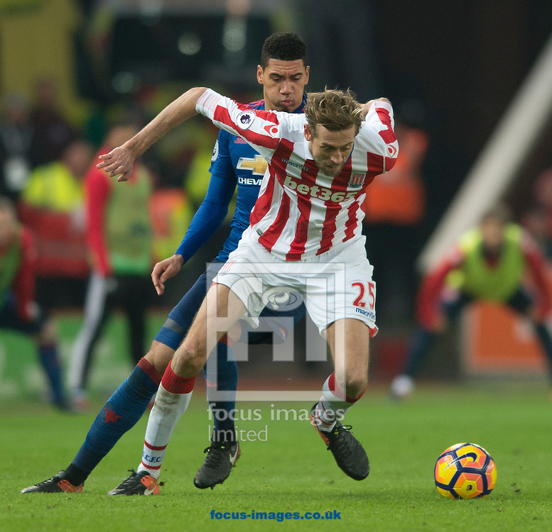 Peter Crouch of Stoke City (nearest) and Chris Smalling of Manchester United challenge for the ball during the Premier League match at the Bet 365 Stadium, Stoke-on-Trent<br /> Picture by Russell Hart/Focus Images Ltd 07791 688 420<br /> 21/01/2017