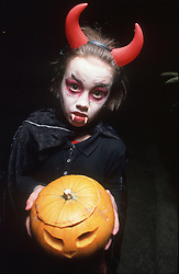 Young girl dressed up for Halloween with face painted as devil; holding a pumpkin,