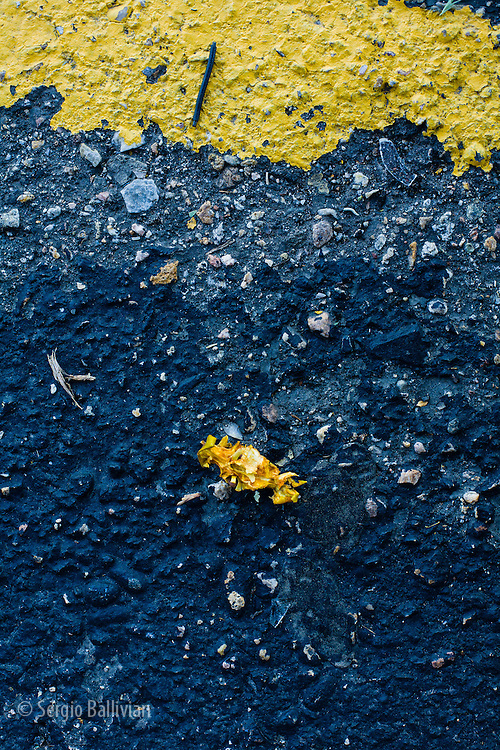 A bright yellow painted sign on a parking lot stands out in contrast to the worn-out asphalt, like abstract art.