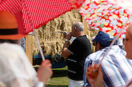 Photo by Andrew Tobin/Tobinators Ltd - 07710 761829 - A competitor takes aim as the crowd shelter from the sun under colourful umbrellas during the World Peashooting Championships held at Witcham, Cambridgeshire, UK on 13th July 2013. Run in conjunction with the village fair, the Championships have been held in Witcham since 1971 when they were started by a Mr Tyson, the village schoolmaster, in order to raise funds for the village hall.Competitors come from as far afield as the USA and New Zealand to attempt to win the event. The latest technology is often used, including laser sights and titanium and carbon fibre peashooters. All peashooters must conform to strict length rules, not exceeding 12 inches, and have to hit a target 12 feet away. Shooting 5 peas at a plasticine target attached to a hay bale, the highest scorers move through the initial rounds to a knockout competition, followed by a sudden death 10-pea shootout.