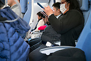 Asian person with protective face mask in airplane seat