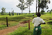 An African student watches his peers play baseketball in the distance at Kuna Primary School in North Kamagambo, Kenya.