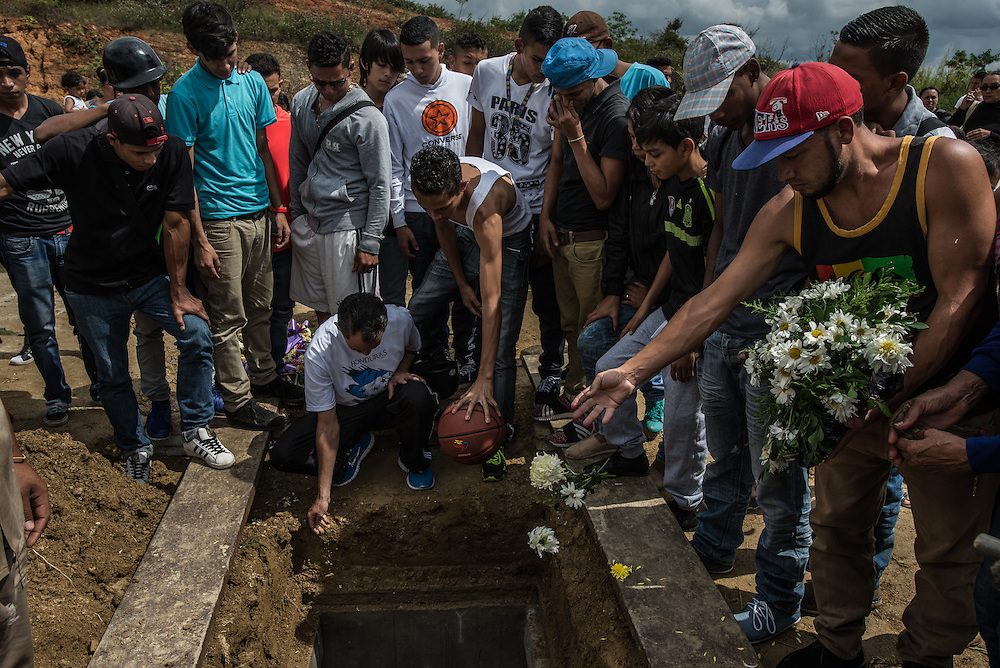 CARACAS, VENEZUELA - NOVEMBER 20, 2016: Family and friends mourn the death of Jon Quintero, a 20-year old motorcycle mechanic and basketball player, who was killed during an OLP operation in Ciudad Caribe. Family and community members are outraged, claiming that he was not involved in any sort of crime, and was does not even live in Ciudad Caribe, he was there visiting a friend during the raid.  Police claim he was killed during a confrontation, saying  he shot at police during the raid, however several witnesses interviewed by The New York Times said Mr. Quintero cooperated with police, that no shootout occurred.  President Maduro ordered regular OLP operations to be held across the country to combat violent crime, however communities affected regularly claim only innocent people are being killed then falsely portrayed as criminals to justify their deaths. PHOTO: Meridith Kohut for The New York Times