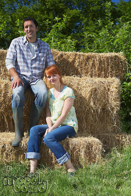 Couple sitting on hay bales in countryside portrait