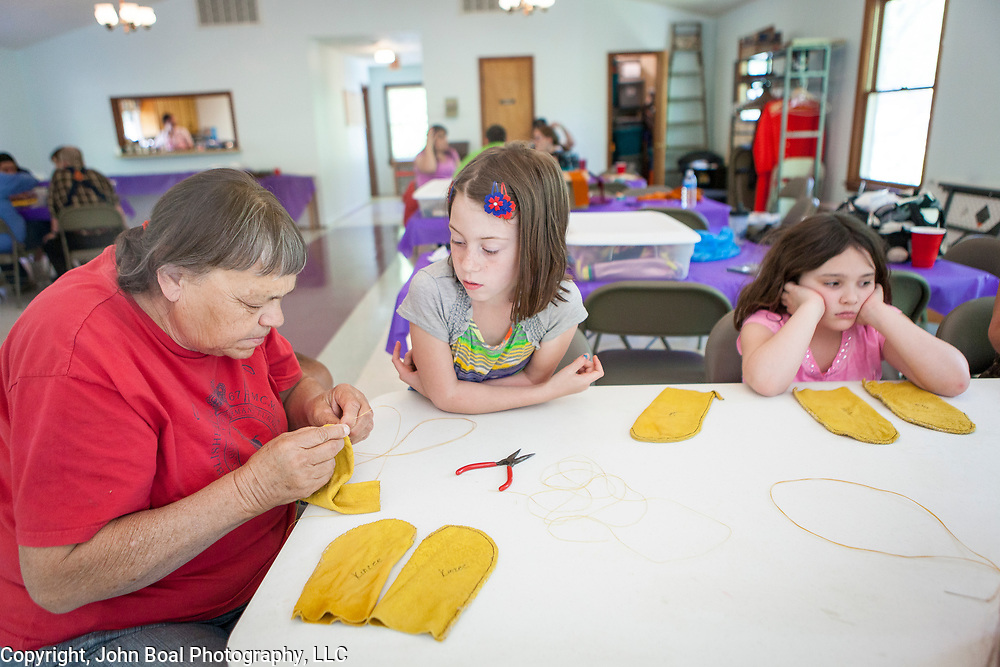 Bertie Branham, left, teaches Taylor Branham, center and Makayla Branham, how to sew moccasins during the weekly culture class at the Monacan Tribal Center, on Saturday, May 3, 2014.  Bertie, Taylor and Makayla are not directly related, but Branham is a common surname in Monacan Nation.