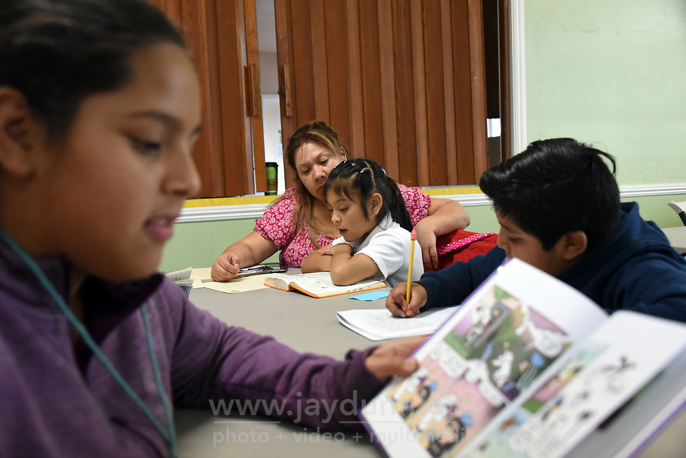From left, Maria Flores, LIFE tutor Sylvia Gonzales, Desiree Garcia and Alexander Lopez work quietly at their respective literacy levels.