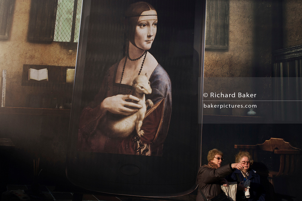 Billboard advertising Leonardo da Vinci's Portrait of Cecilia Gallerani (Lady with an Ermine) above  London tourists at National Gallery.