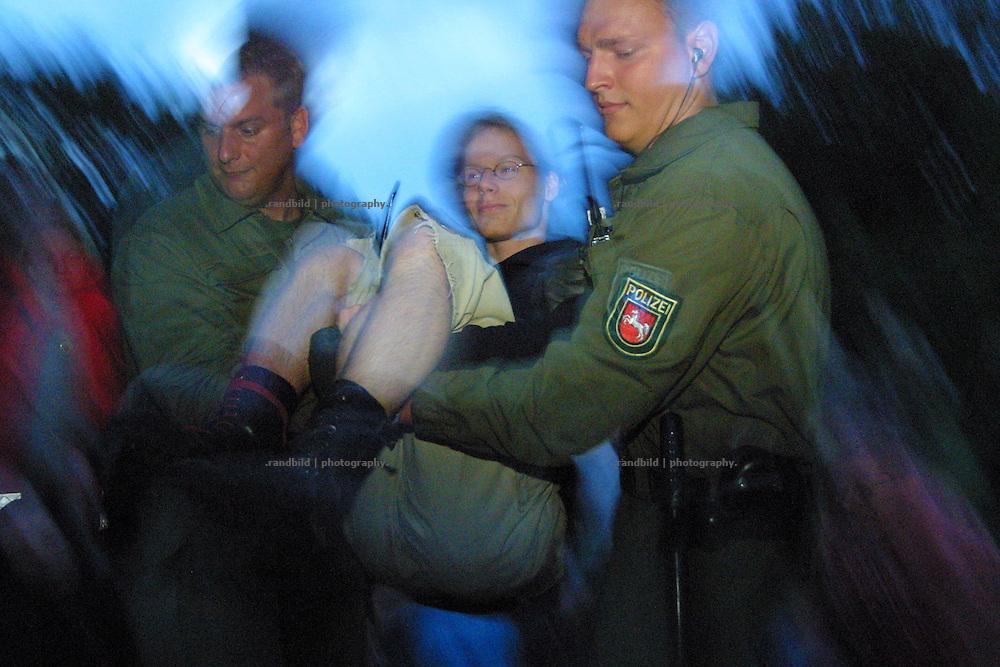 Ein Demonstrant wird von Polizisten von den Gleisen getragen. Er hatte zuvor mit anderen die Schienenstrecke für Castortransporte blockiert