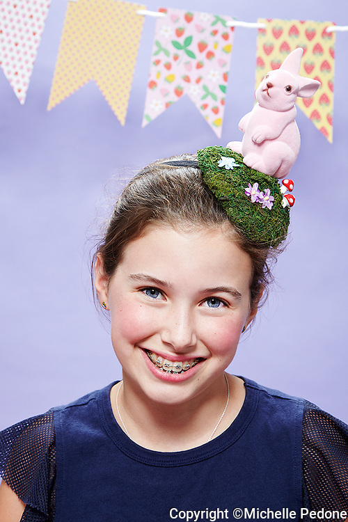 12 year old girl with braces wearing a pink bunny hat against lavender seamless. Photographed at the Photoville Photo Booth September 20, 2015