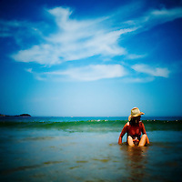 A young woman wearing a bikini and hat sitting in shallow water on a beach with blue sky