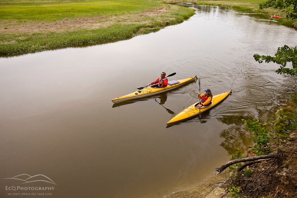 A couple kayaks the upper reaches of the York River in York, Maine.  High tide.