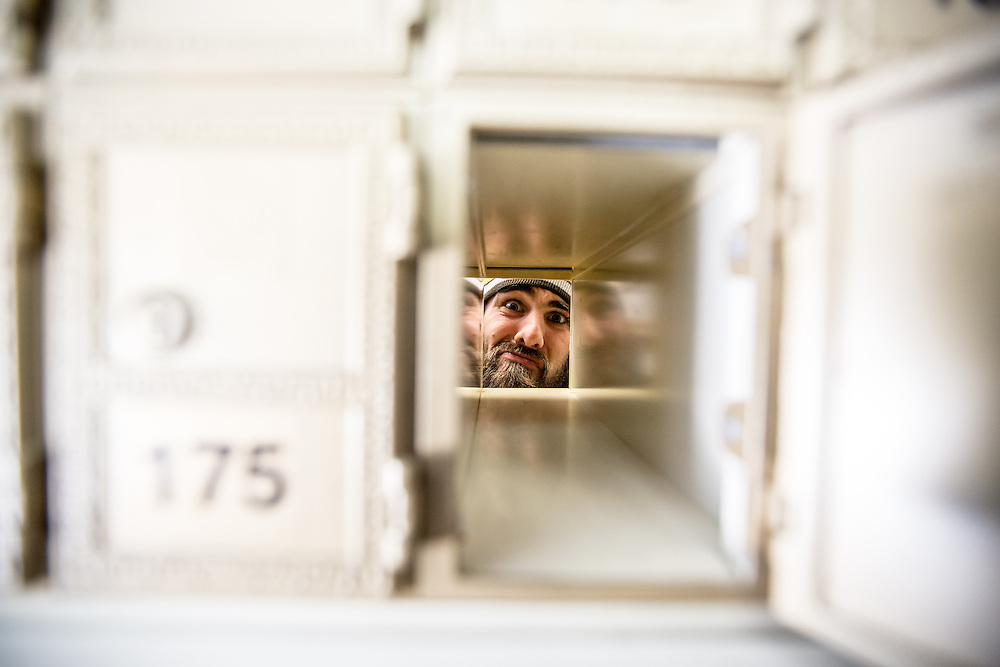 Adam Simar peaks through a mailbox while sorting deliveries at the UPS Store in San Francisco,CA. (Charles Hall/challphotos.com)