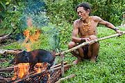 Mentawai indigenous man burning a piglet (Indonesia).
