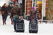 Twee reizigers ploeteren bij de Servetstraat in Utrecht met hun koffers door de sneeuw.<br /> <br /> Two travellers are walking with their suitcases in the snow at the Servetstraat Utrecht.