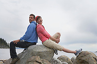 Couple sitting back to back on rocks by ocean portrait