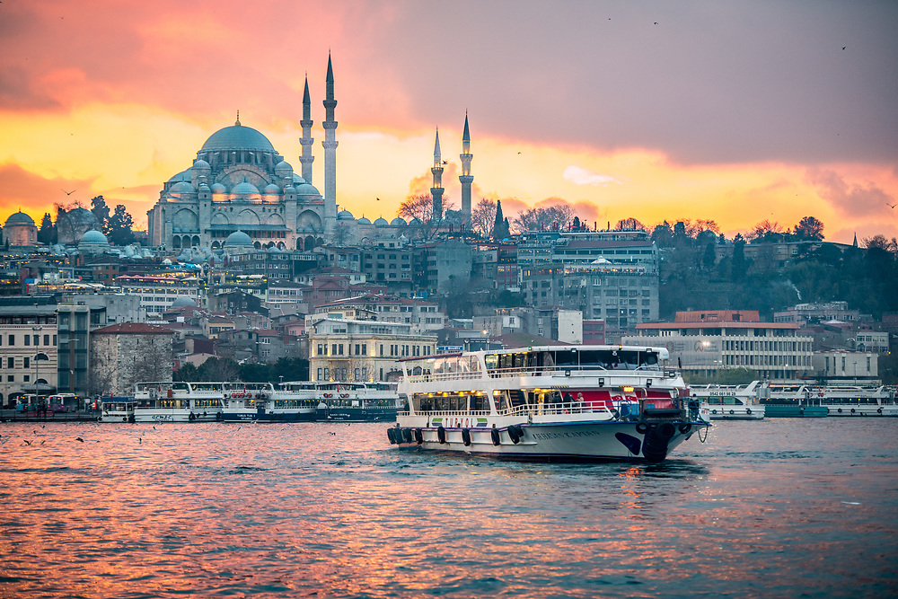 As the sunsets, a ferry boat glides across the waters of the Golden Horn with the Suleymaniye Mosque and the city of Istanbul, Turkey in the background.