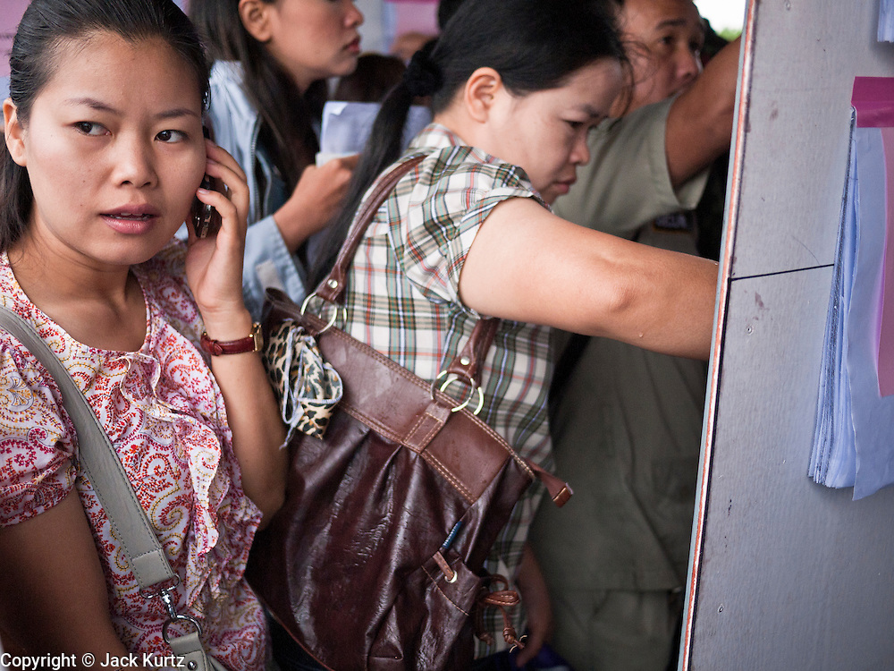 26 JUNE 2011 - CHIANG MAI, THAILAND:  A woman talks on her mobile phone while looking for her polling station at the voting center in Chiang Mai, Thailand, Sunday. Absentee voting was Sunday, July 26 in Thailand's national election. The regular voting is Sunday July 3. In Chiang Mai, center of the powerful Red Shirt opposition movement and their legal party Pheua Thai, turnout was heavy despite a steady rain. Thailand's democracy will be tested in the election, which is the most bitterly fought contest in Thai political history. The Pheua Thai represents people loyal to fugitive former Prime Minister Thaksin Shinawatra, ousted by a military coup in 2006. The ruling Democrats have governed Thailand in one form or another nearly continuously since 1932. Pre-election polls show Pheua Thai leading but not by enough to rule without forming a coalition with smaller parties.   PHOTO BY JACK KURTZ
