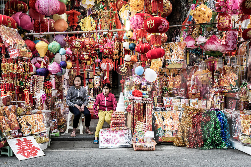 Colorful Tet decorations sold along Hang Ma Street in Hanoi's Old Quarter surround young vendors,  Vietnam, Southeast Asia
