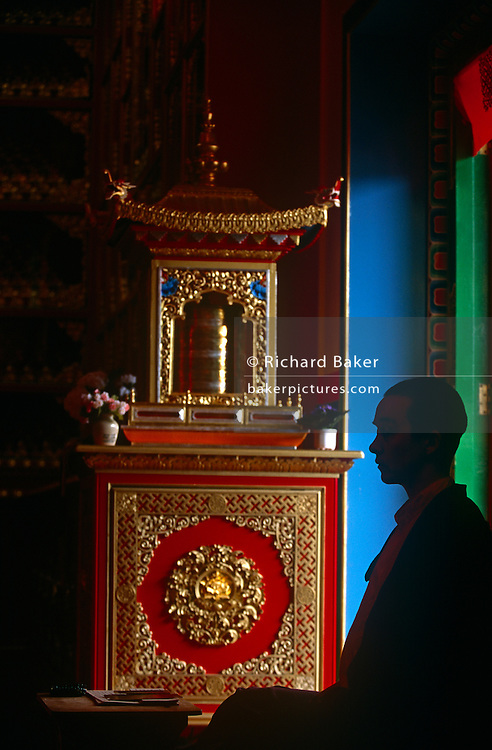 A westerner nun practicing Tibetan-Buddhism meditates in silence at a shrine in the Kagyu Samye Ling Buddhist retreat centre,