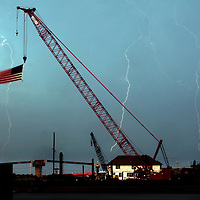 Lightning bolts streaks out of the sky at the foot of Barh's Marina with the Highlands Bridge which is under construction to the right.