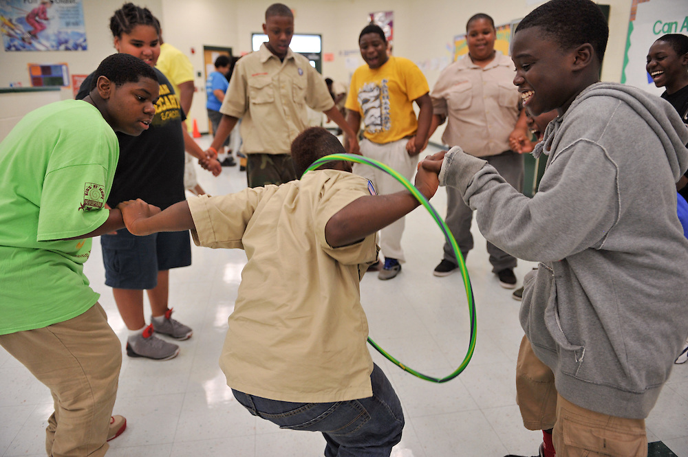 Boy Scout Troop 772 boys pass a hoop to each other, as they try not to break their hold, during a meeting April 16, 2014. The purpose of the exercise was to build teamwork and communication. (XAVIER MASCAREÑAS/TREASURE COAST NEWSPAPERS)