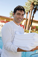 Portrait of man carrying towels at health spa