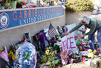 "A woman places a ""Peace"" sign at a memorial outside the offices of congresswoman Gabrielle Giffords in Tucson, Arizona January 9, 2011. Charges against the suspect in a shooting rampage that wounded Giffords and killed six others were expected on January 9, FBI Director Robert Mueller said.  REUTERS/Rick Wilking (UNITED STATES)"
