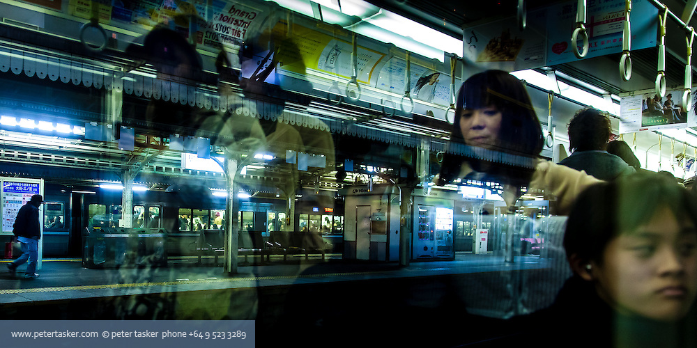 Train passengers and window reflections. Japan.