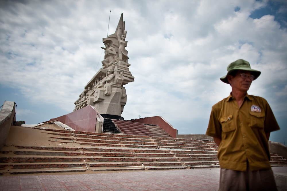 A construction worker stands next to a gigantic socialist monument in Long An Province, Vietnam.