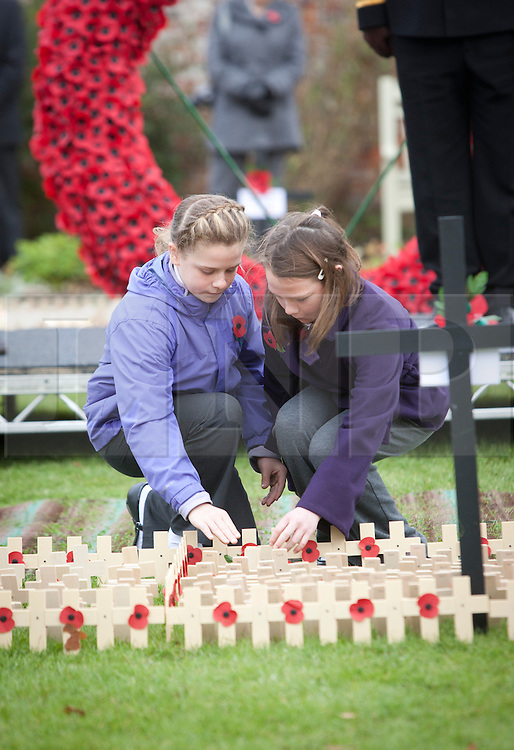 © Licensed to London News Pictures. 09/11/2012, Royal Wootton Bassett. Two young girls plant a cross following a 2 minute silence at the Field of Remembrance today tin Royal Wootton Bassett. Photo credit : Alison Baskerville/LNP