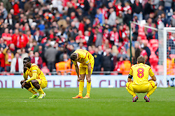 Liverpool players Mario Balotelli, Jordan Henderson and Steven Gerrard look dejected after Aston Villa win the match 2-1 to reach the 2015 FA Cup Final - Photo mandatory by-line: Rogan Thomson/JMP - 07966 386802 - 19/04/2015 - SPORT - FOOTBALL - London, England - Wembley Stadium - Aston Villa v Liverpool - FA Cup Semi Final.