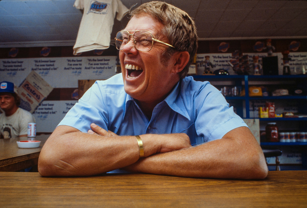 """Billy Carter laughs while sitting at the bar in his Plains, Georgia gas station. William Alton - Billy - Carter (March 29, 1937 – September 25, 1988) was an American farmer, businessman, brewer, and politician, and the younger brother of U.S. President Jimmy Carter. Carter promoted Billy Beer and was a candidate for mayor of Plains, Georgia. Carter was born in Plains, Georgia, to James Earl Carter Sr. and Lillian Gordy Carter. He was named after his paternal grandfather and great-grandfather, William Carter Sr. and William Archibald Carter Jr. respectively. He attended Emory University in Atlanta but did not complete a degree. He served four years in the United States Marine Corps, then returned to Plains to work with his brother in the family business of growing peanuts. In 1955, at the age of 18, he married Sybil Spires (b. 1939), also of Plains. They were the parents of six children: Kim, Jana, William """"Buddy"""" Carter IV, Marle, Mandy, and Earl, who was 12 years old when his father died."""