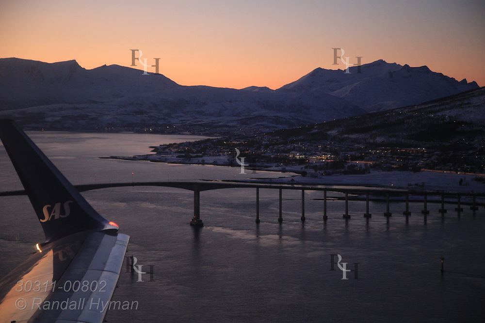 Aerial view from Scandinavian Airlines jet on a January afternoon of Kvaloya island and bridge across from Tromso, Norway.