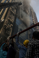 March 28, 2019 - Dhaka, Bangladesh - At least 19 people, including a Sri Lankan citizen, were killed and 70 others injured in a fire that broke out at FR Tower in Dhaka's Banani area this afternoon 28 March 2019. The fire broke out on the eighth floor of the 22-storey building on Banani Road 17 around 1:00pm and engulfed other floors immediately. The cause of the fire could not be known immediately. (Credit Image: © Khandaker Azizur Rahman Sumon/NurPhoto via ZUMA Press)