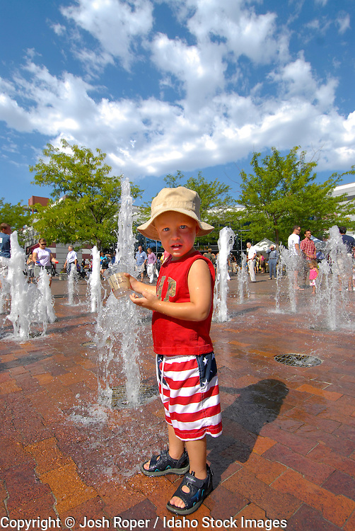 Idaho, Boise. A young boy plays in the fountain on The Grove, in Downtown Boise.